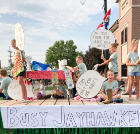 These Busy Jayhawkers 4-H members ride on their float during the Nemaha County Fair parade.