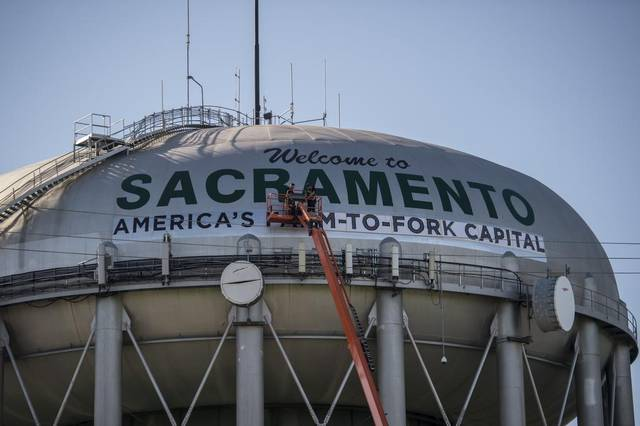 "Crews work on the Sacramento water tower visible from Interstate 5 on Wednesday, March 8, 2017, in Sacramento, Calif. The water tower which read ""Welcome to Sacramento City of Trees"" will now read ""America's farm-to-fork Capital."""
