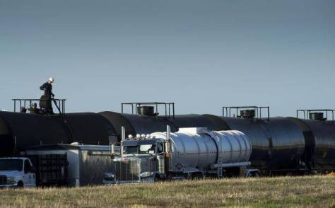 A tanker truck is filled from railway cars containing crude oil at McClellan Park in 2014.