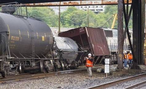 In this July 24, 2014 file photo, an investigator photographs the scene where a locomotive and cars carrying crude oil went off the track beneath the Magnolia Bridge in Seattle.