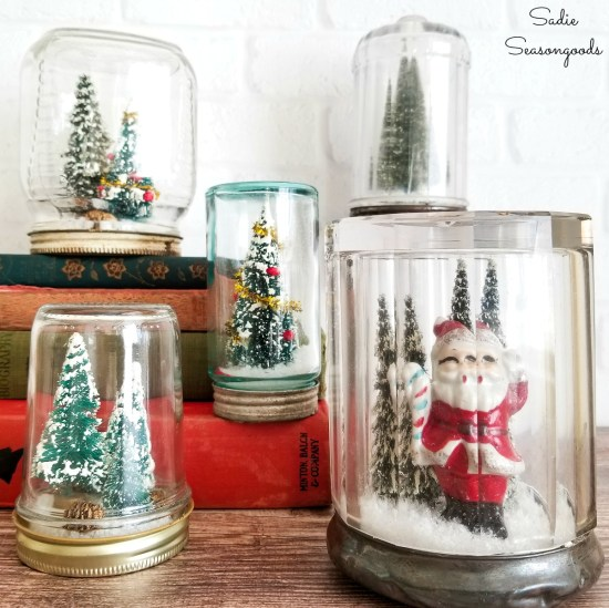 Snowglobes or snow globes and vintage Christmas decorations in antique mason jars