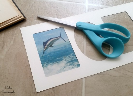 Cutting out vintage prints from a thrift store book to be framed in a multi photo frame or collage photo frame by Sadie Seasongoods