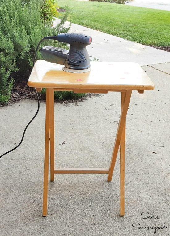Using an orbital sander to remove the lacquer from a wooden tray table