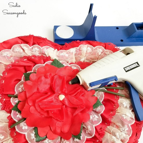 Fixing the flowers on vintage Valentine decorations with a hot glue gun
