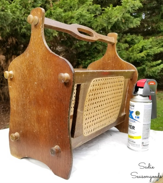 Spray painting a vintage magazine rack for upcycling