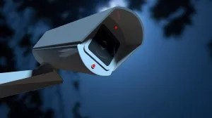 A white wireless surveillance camera with illuminated lights mounted on a wall in the night-time with copy space