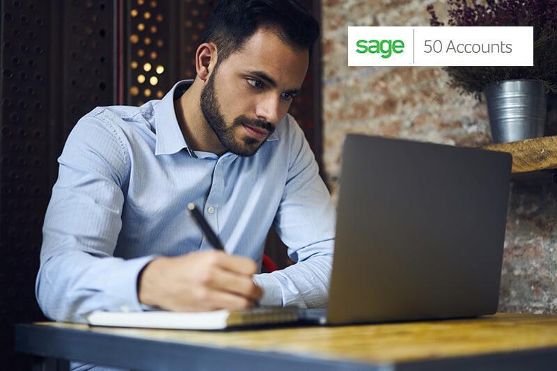 Man sat at computer with sage logo