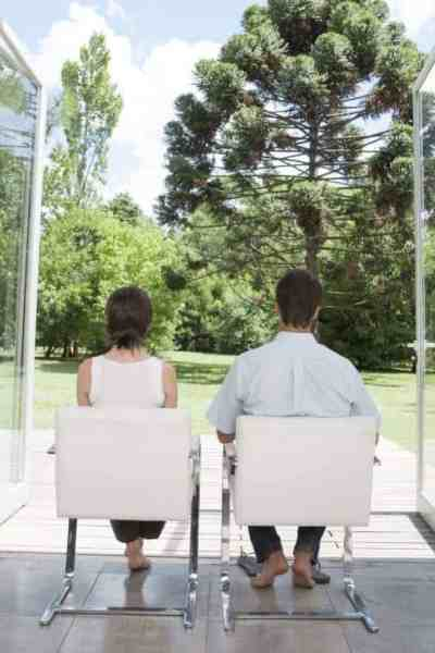 man and a woman sitting in white chairs looking outside to trees through glass doors contemplating granny flats