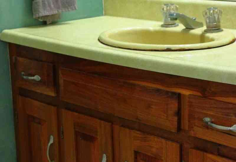 Photo of bathroom vanity with yellow countertop, green wall and wood bathroom cabinet