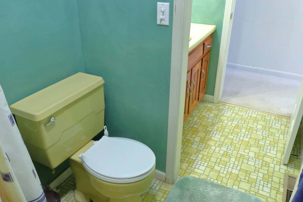 1970's Harvest gold toilet with white lid in green bathroom - before remodel project