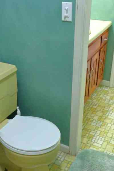 Harvest gold toilet with white lid in green bathroom remodel project