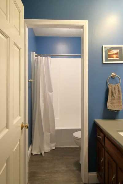 Remodeled 1970s bathroom now has dark blue walls, grey quartz countertop and white plumbing fixtures.