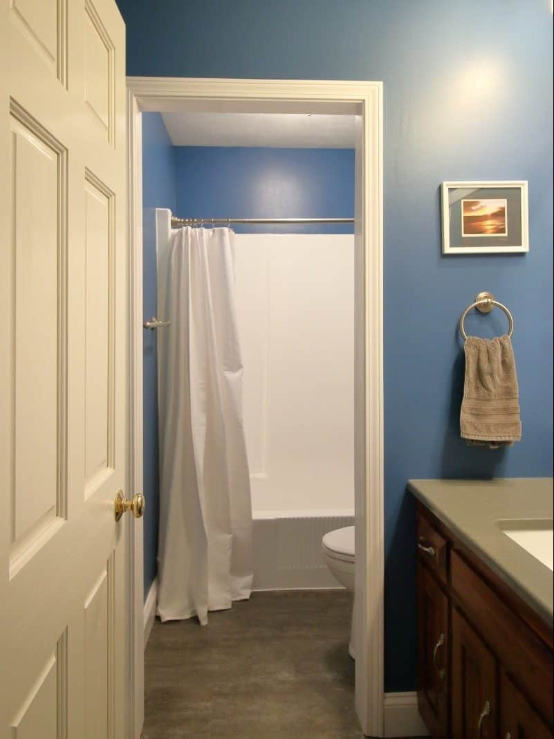 1970s bathroom remodel - updated with dark blue walls, grey vanity, white plumbing fixtures