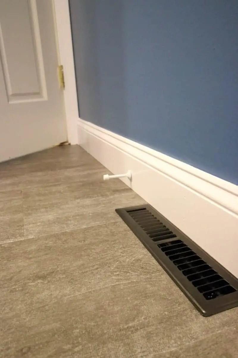 Dark grey luxury vinyl tile, white baseboard and dark blue painted walls.
