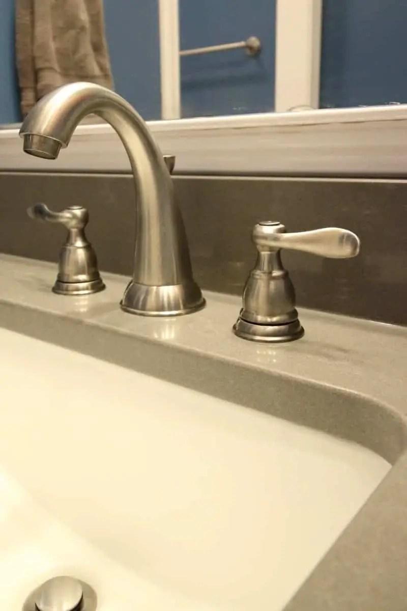 Bathroom makeover with satin nickel faucet and dark grey quartz countertop