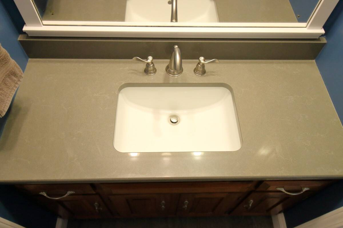 Dark grey quartz countertop, white rectangular sink, satin nickel faucets