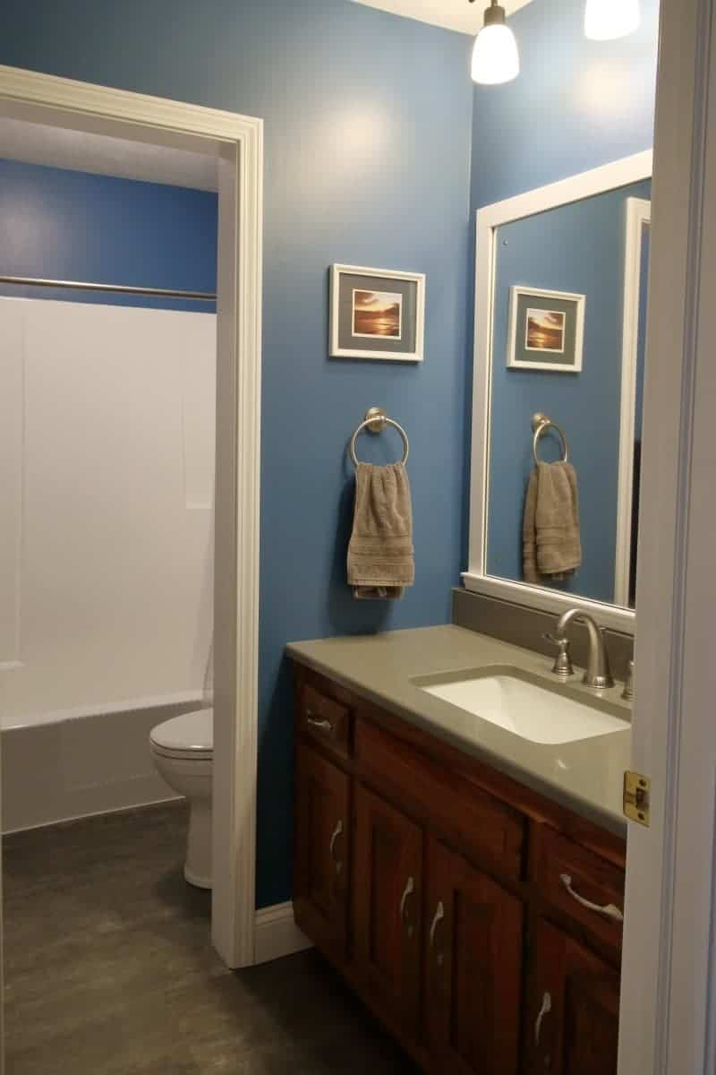 Bathroom remodel after photo of dark blue walls, white trim, dark grey quartz countertop