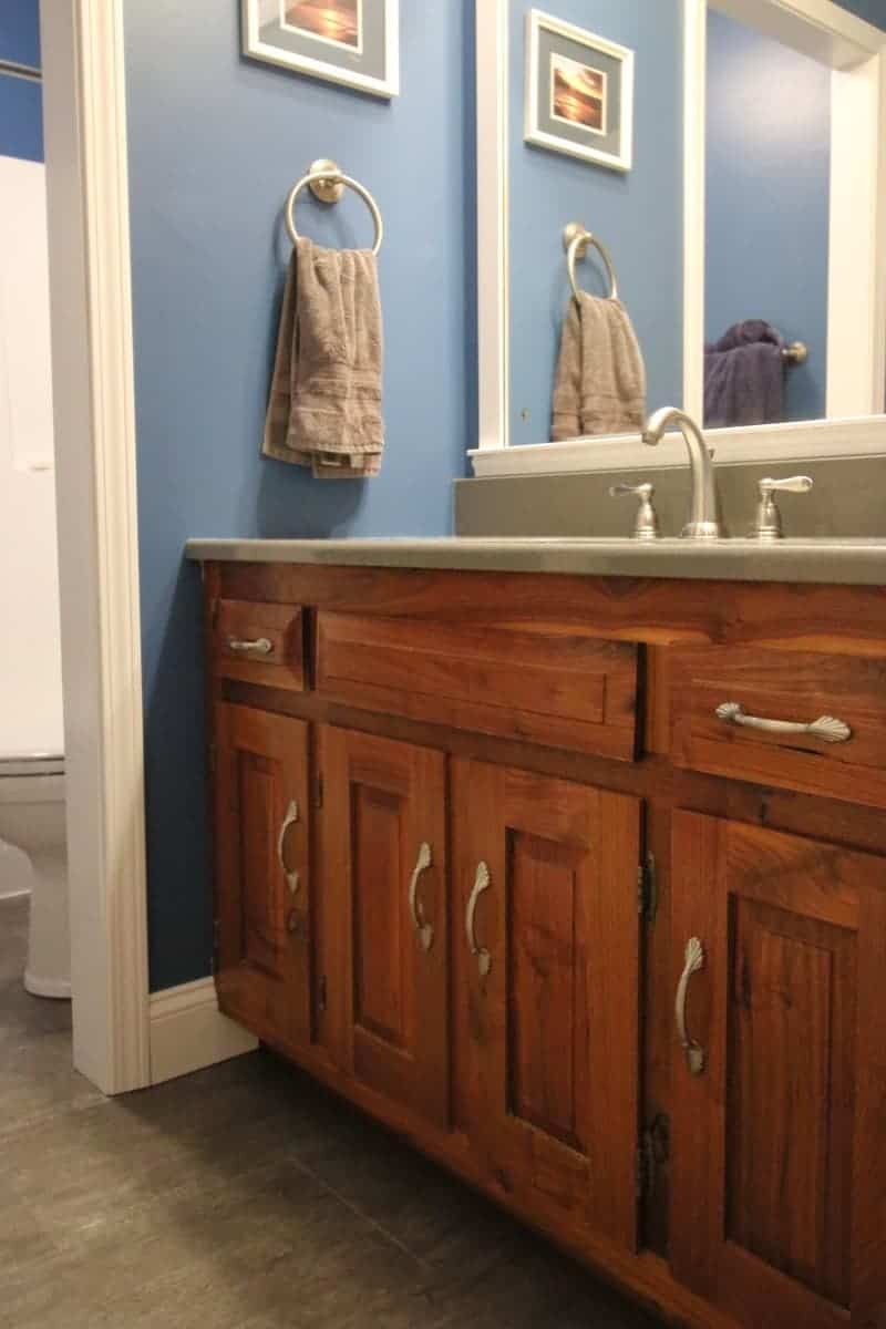 Hickory cabinet, dark grey quartz counter, blue walls in bathroom remodel