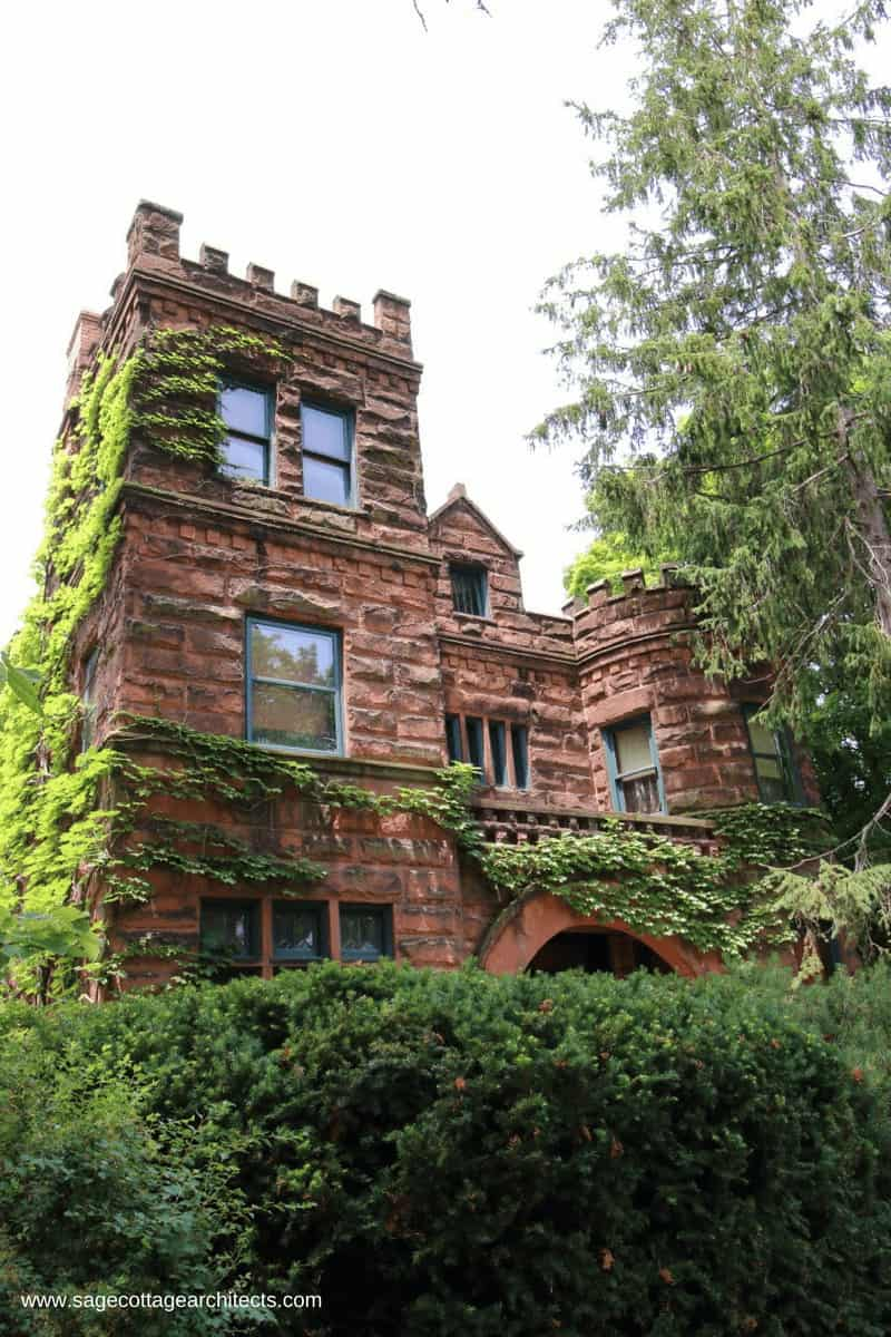 Rough cut exterior stone house with corner tower and battlements, typical of Richardsonian Romanesque homes.