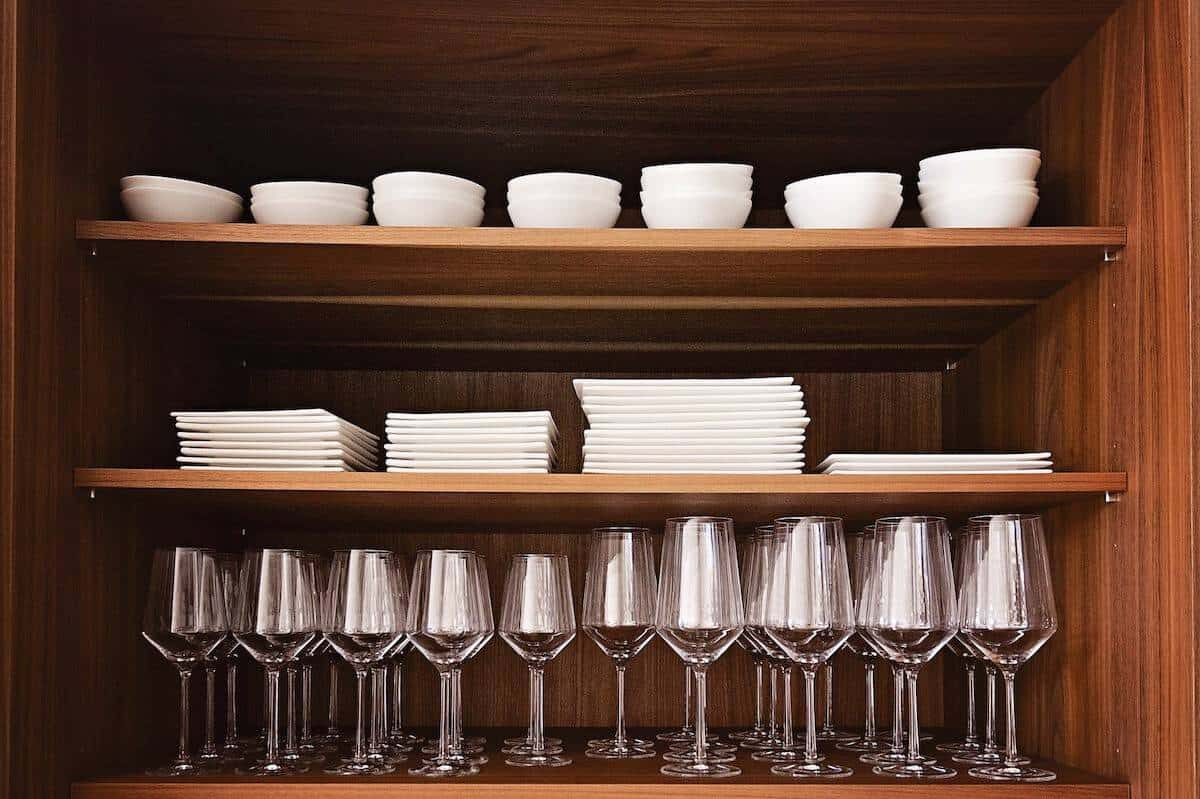 Wooden cabinet with white tableware and wine glasses