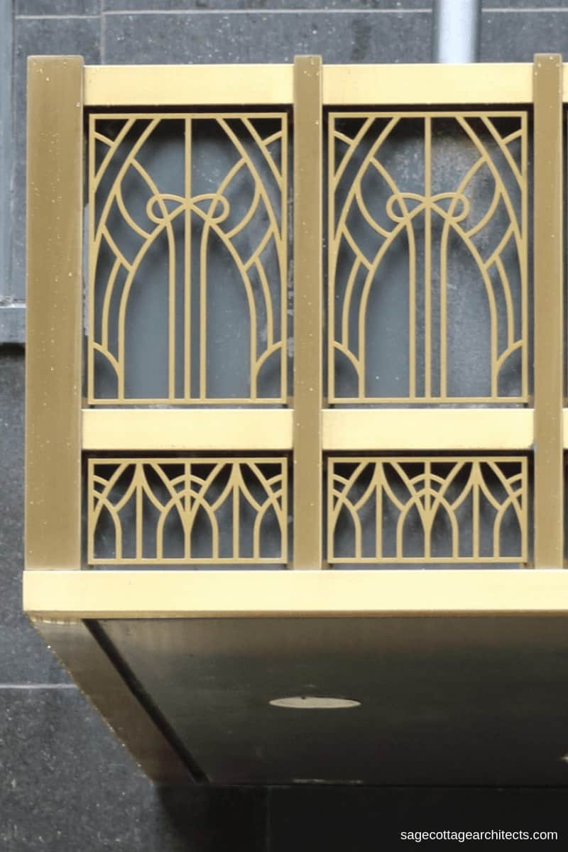 Gold Art Deco entrance canopy on dark grey-green wall