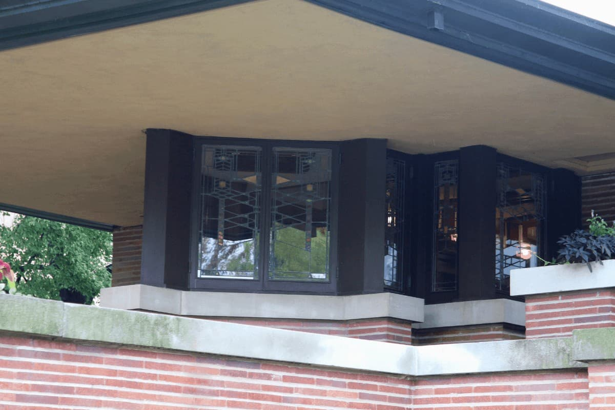 Covered balcony on a Prairie Style home. Red brick, white limestone banding, cream stucco soffit and black window trim.