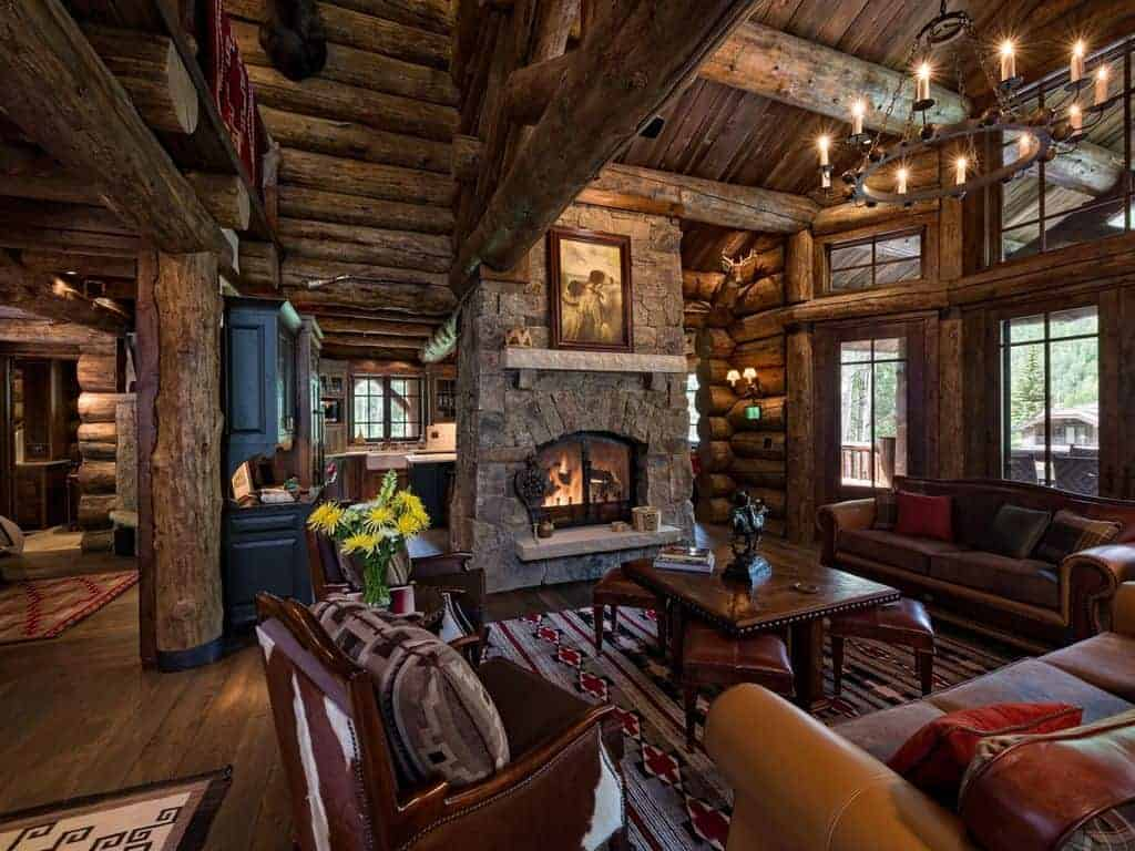 Photo of the interior of a ski vacation lodge home with exposed logs and stone fireplace.