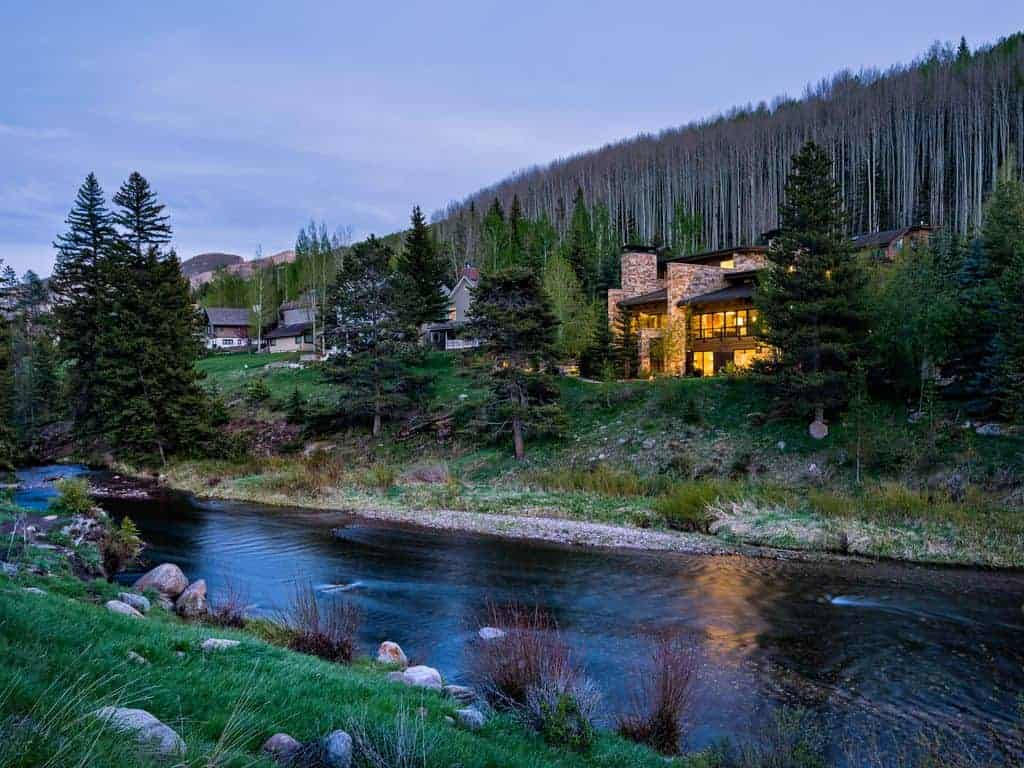 Photo of ski vacation home next to a river, with trees behind.