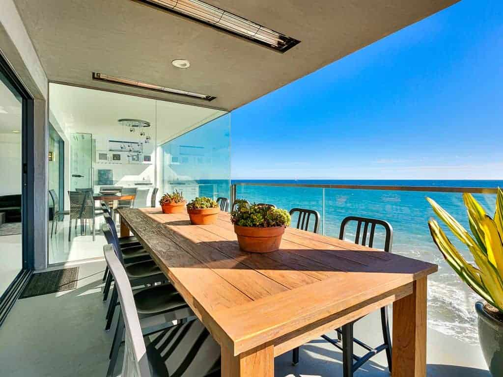 Photo of an outdoor dining table on the balcony of a beach vacation home.