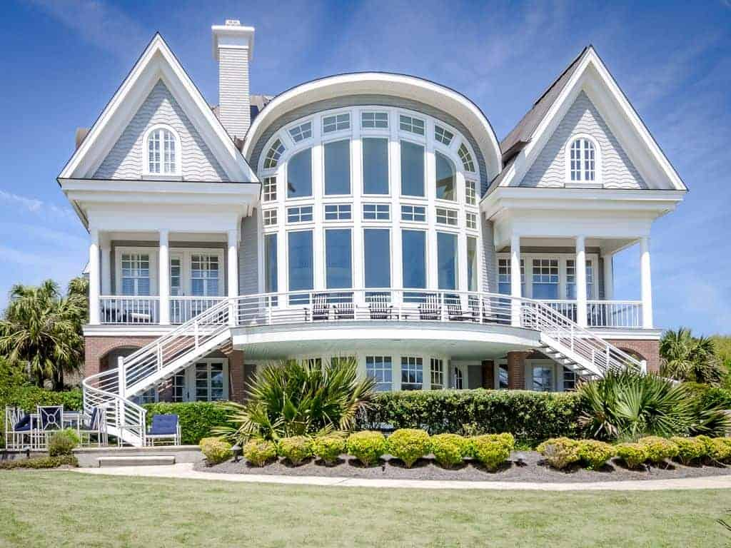 Photo of large beach vacation home with extensive window wall and deck.