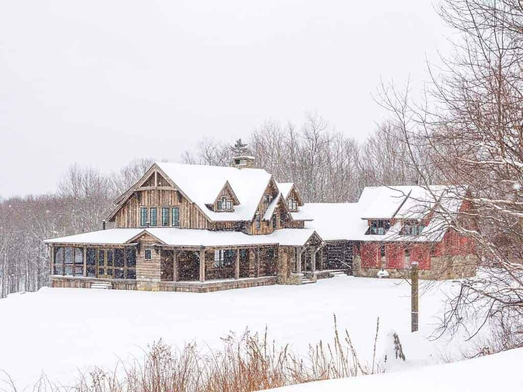 Photo os a farmhouse, that is perfect for a ski vacation, in the snow.