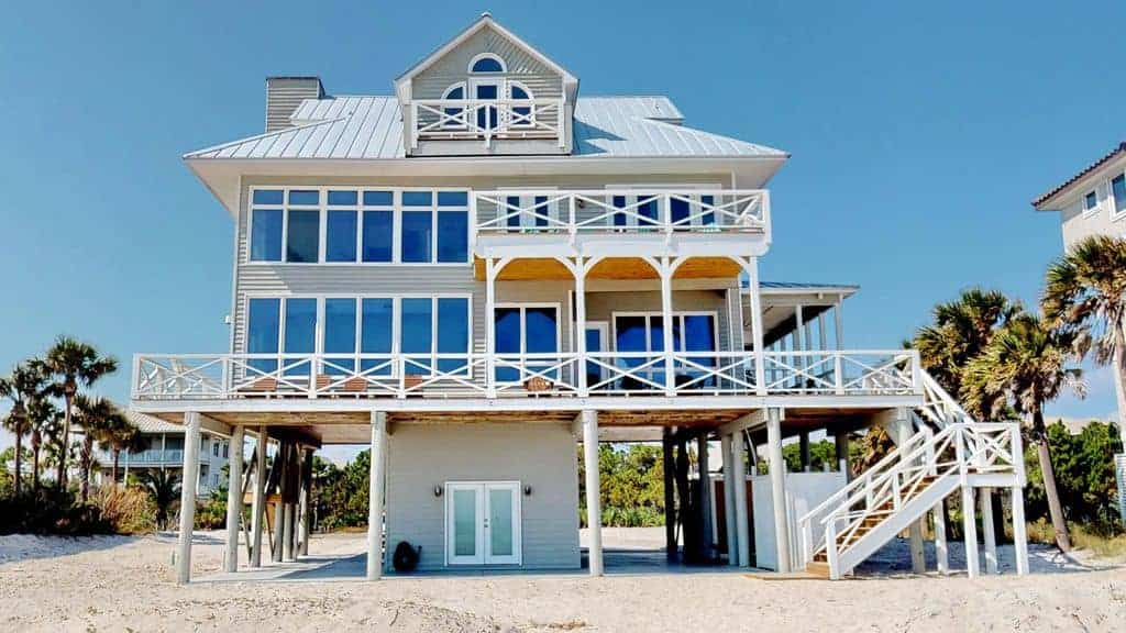 Photo of large beach vacation home, with white porches, on the gulf coast home.