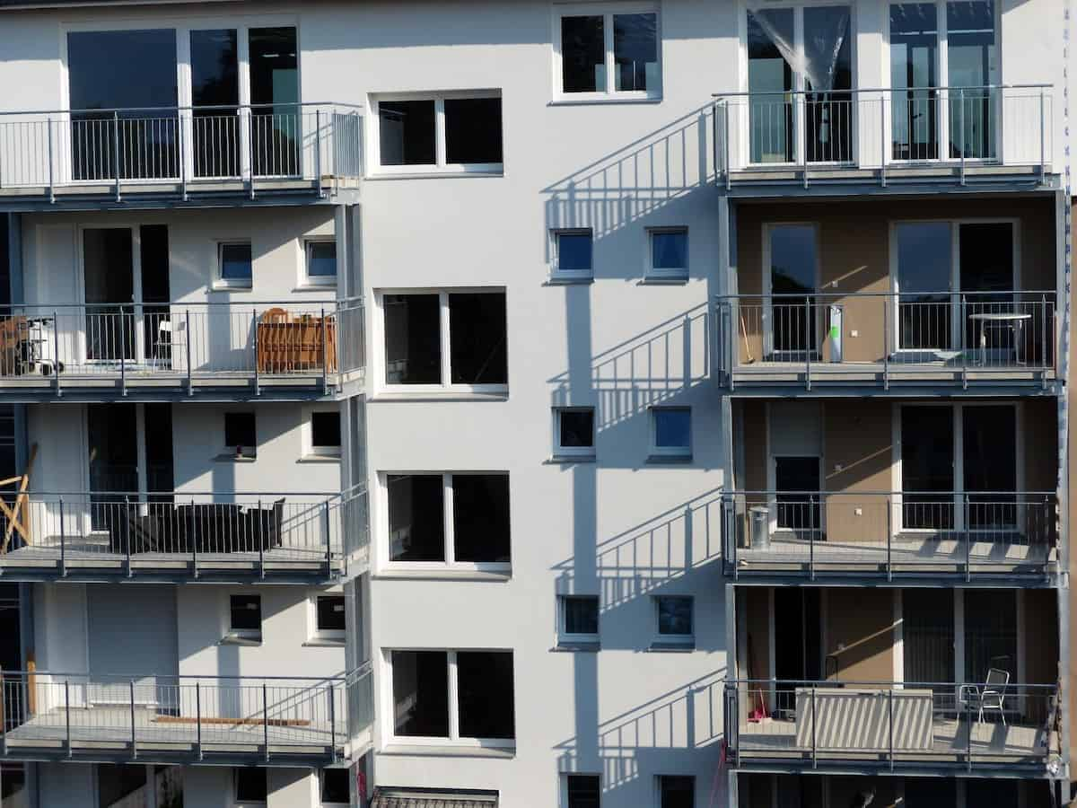 Photo of white building with plain balconies that could benefit from an upgrade of the balcony flooring.
