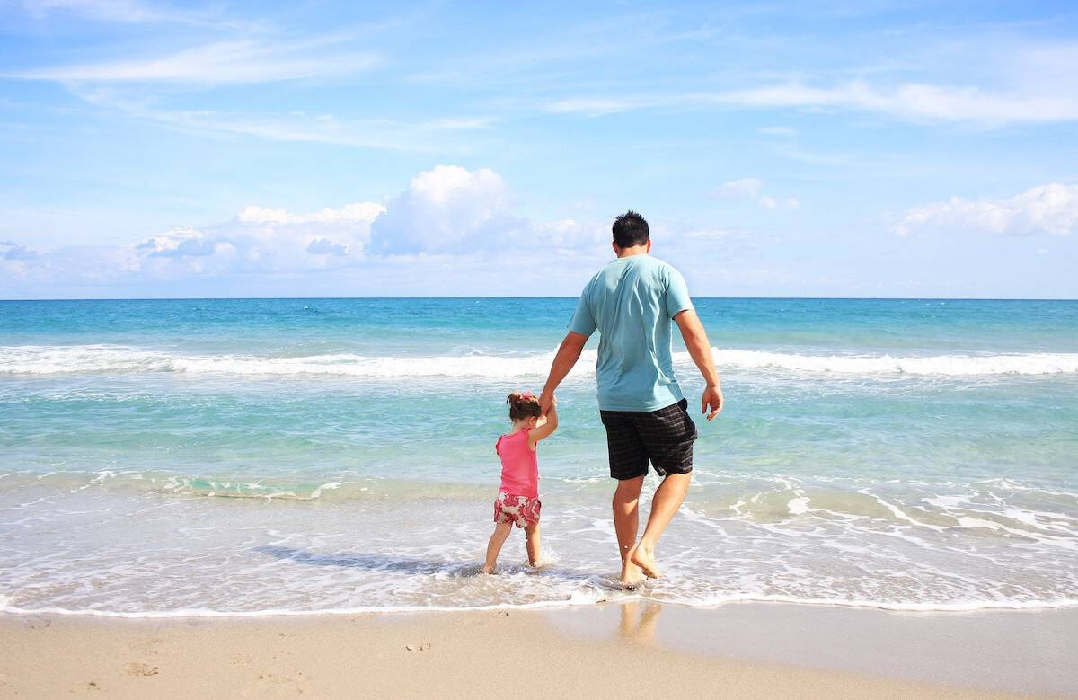 Photo of a dad and young daughter walking along the ocean's edge on a beach vacation.