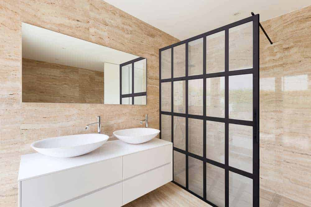 Photo of modern beige bathroom with a black framed glass shower enclosure screen
