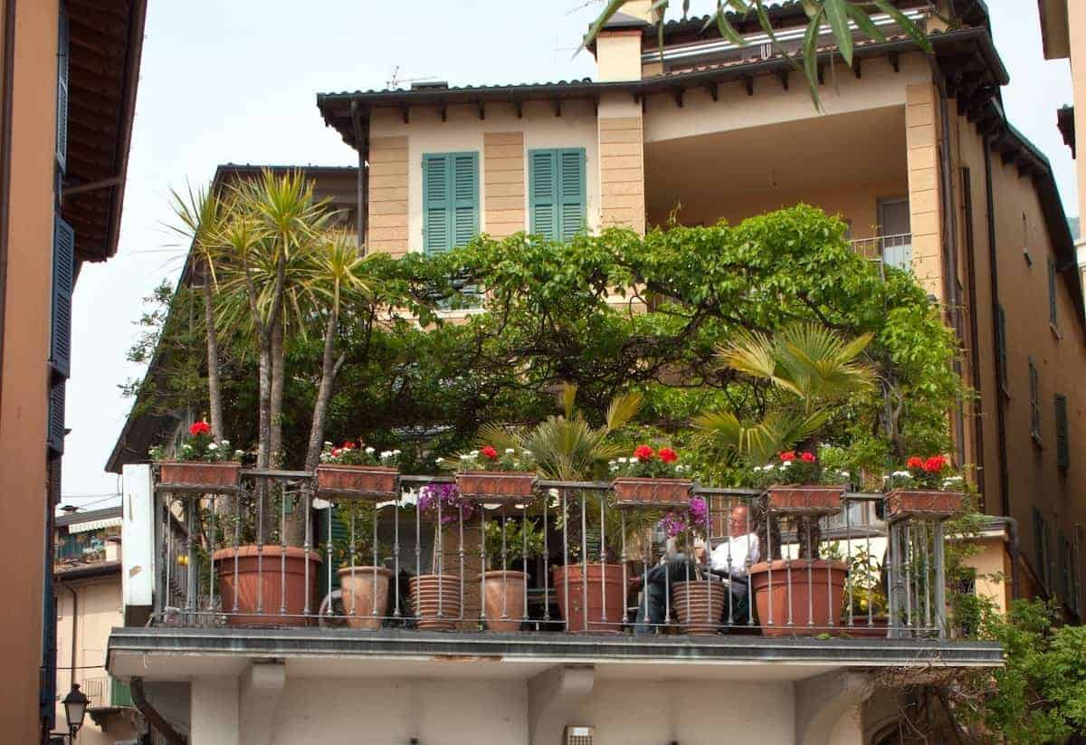 Photo of a man sitting on a balcony, that can inspire many small balcony ideas.