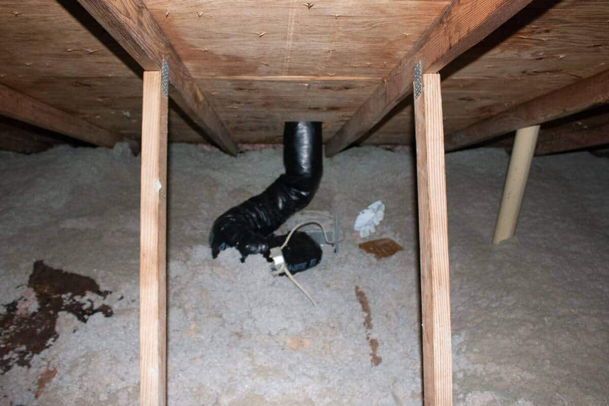 Photo of properly vented bathroom exhaust fan in the attic with an insulated duct going through the roof sheathing.