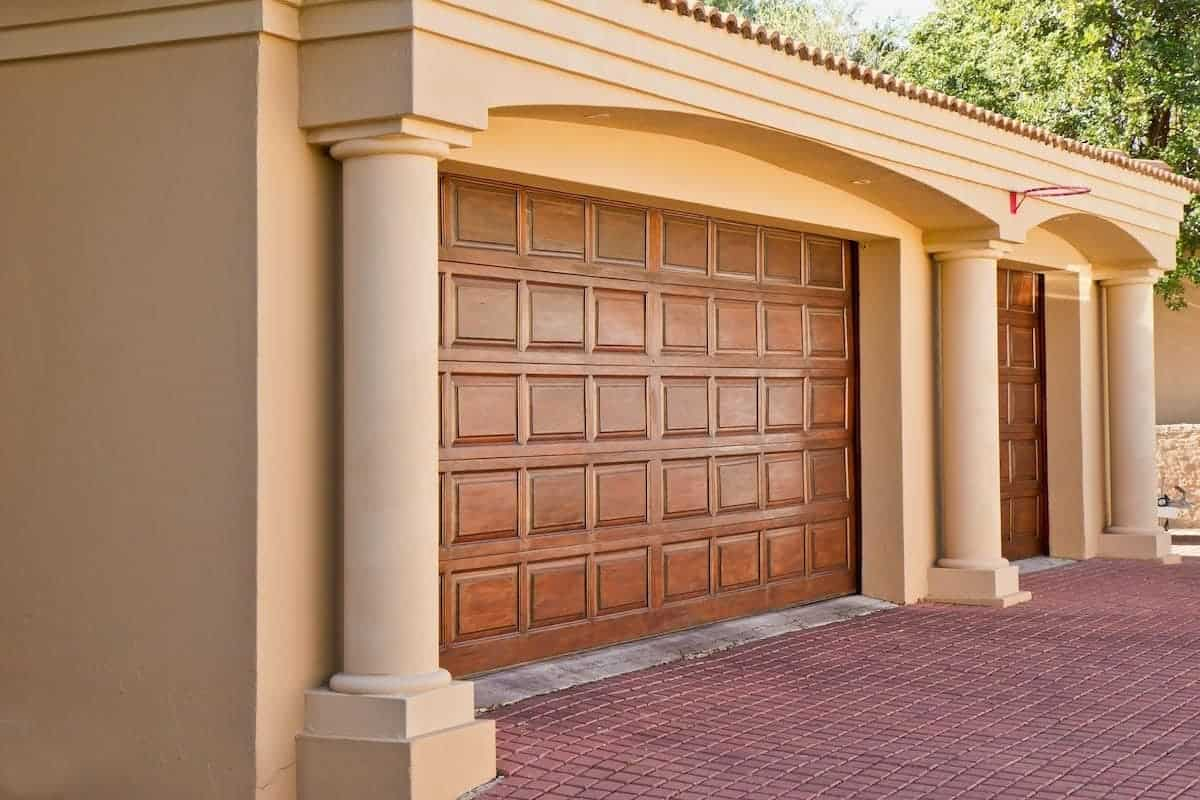 Photo of wood stained garage doors with stucco columns that would make a nice garage conversion.