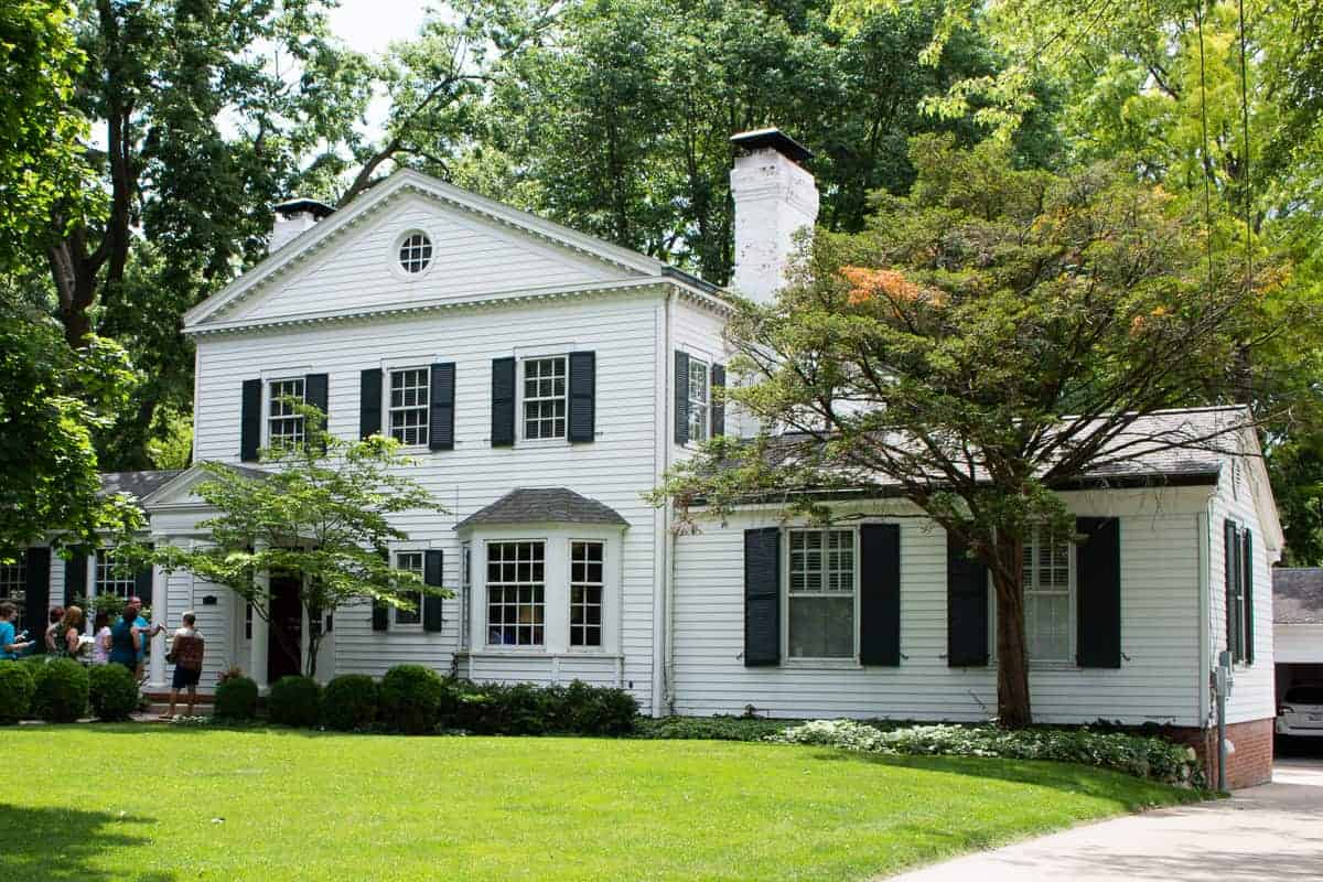 Photo of traditional home with white siding and black window shutters on old house tour.