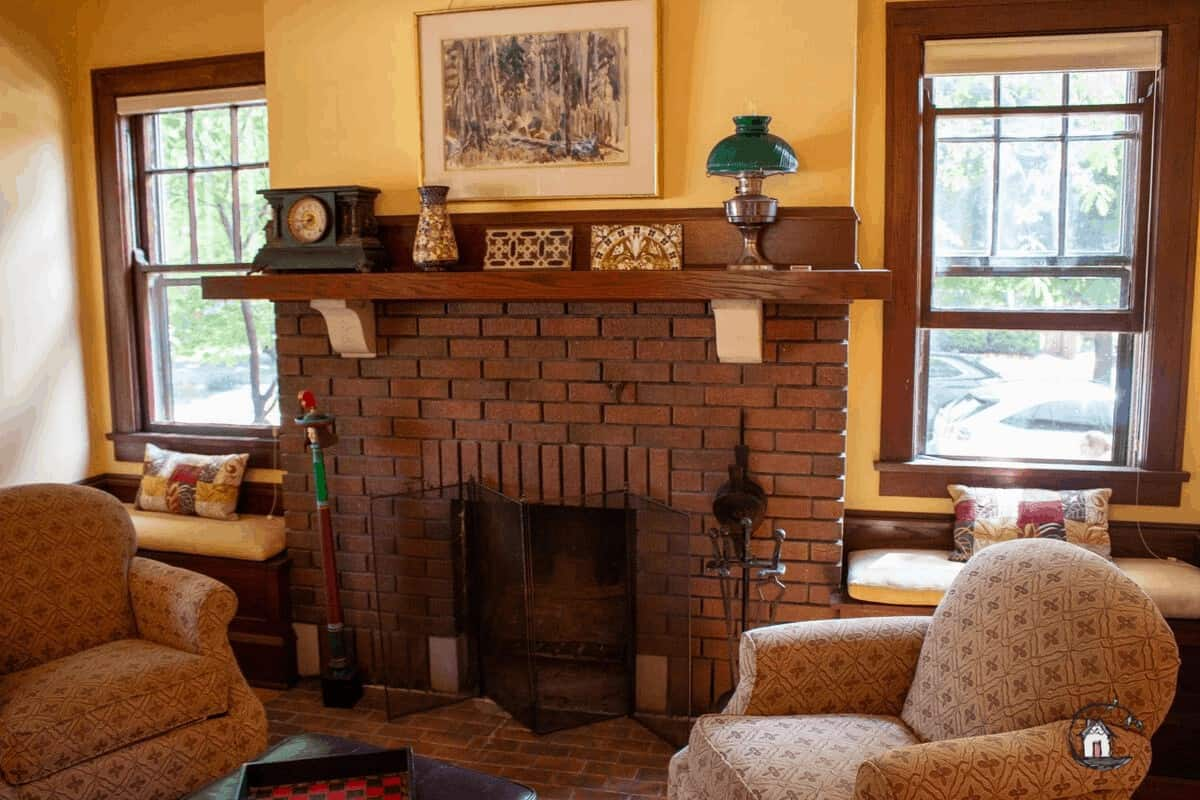 Photo of Arts & Crafts home interior with brick fireplace and windows, as seen on the Old House Society Tour.