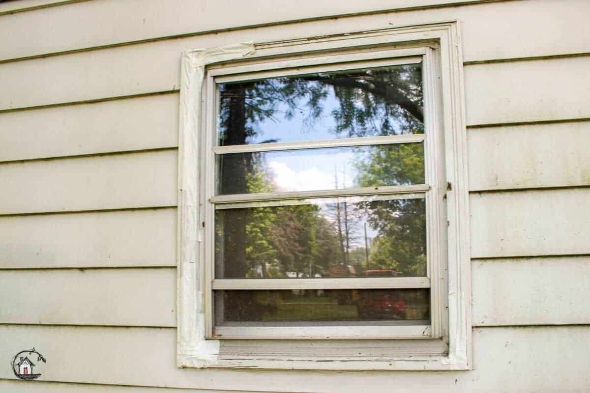 Photo of old window in bad shape, before vinyl window replacement project.