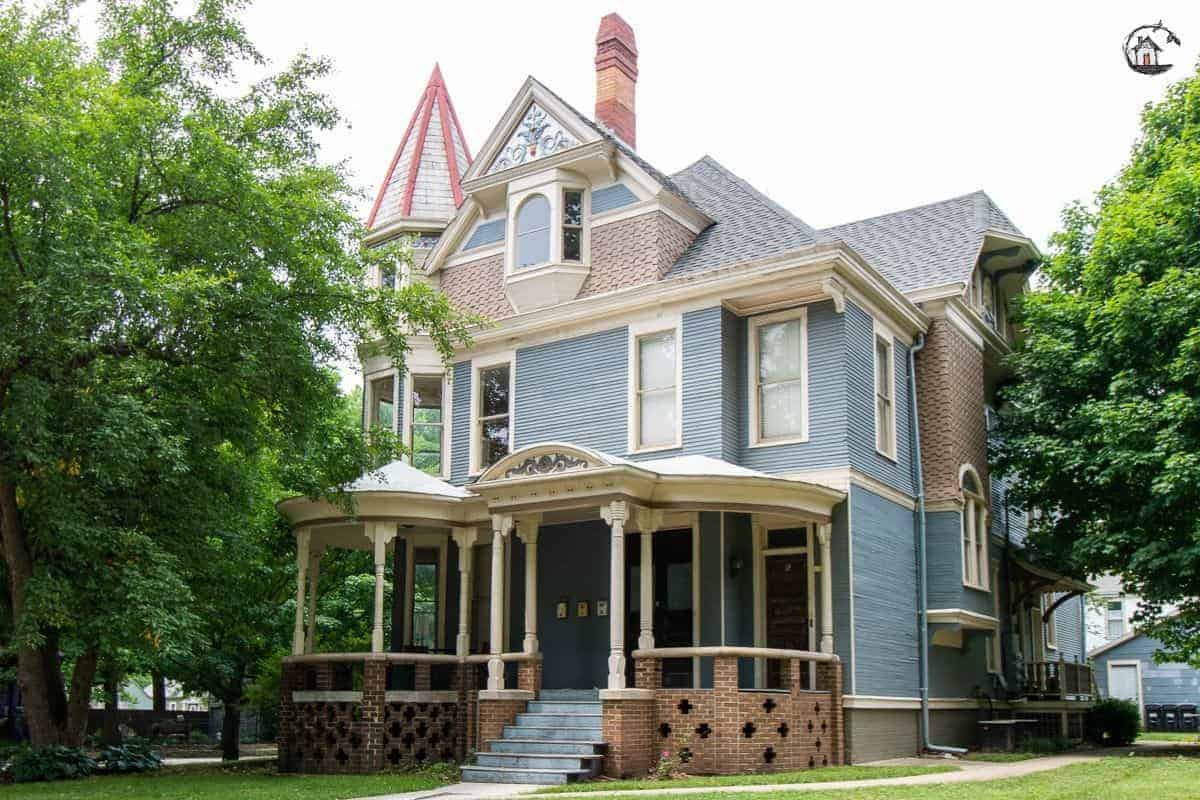 Photo of light blue Victorian home with large front porch in a neighborhood of old houses.