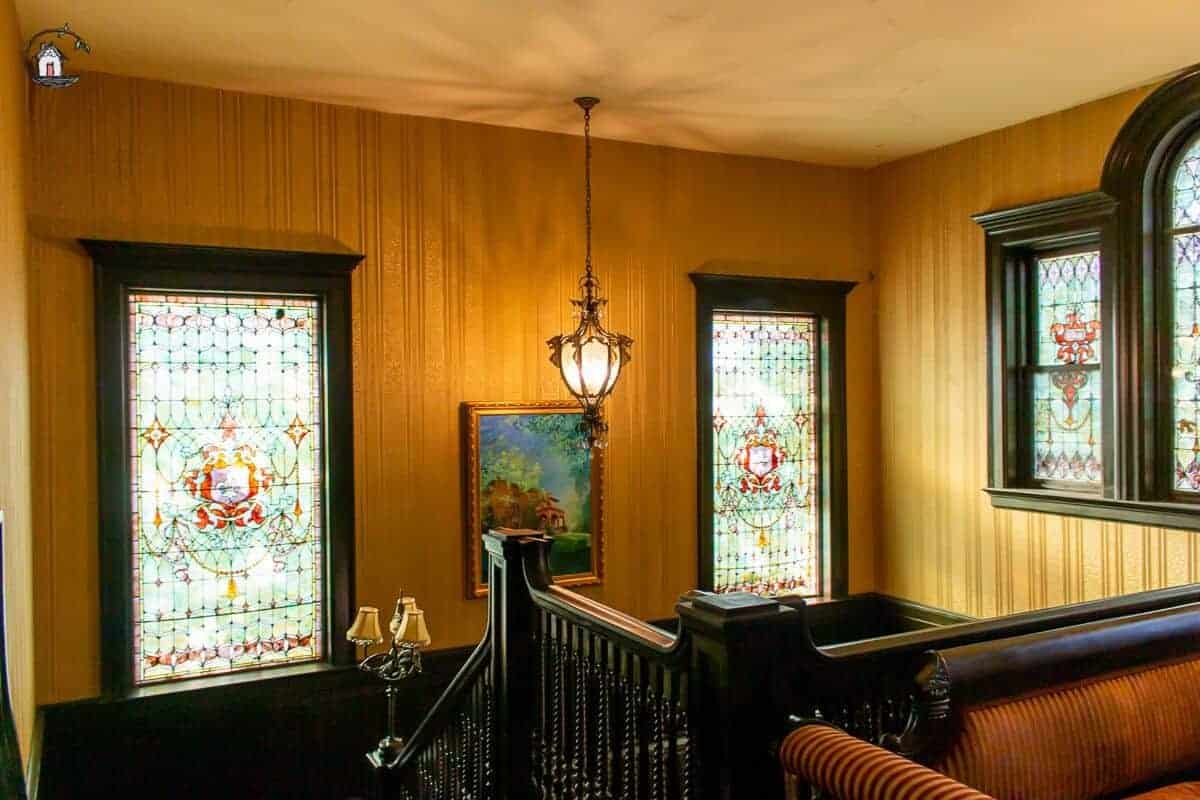 Photo of large stained glass windows, dark wooden handrails and hanging light in the stairway of the Vrooman Mansion.