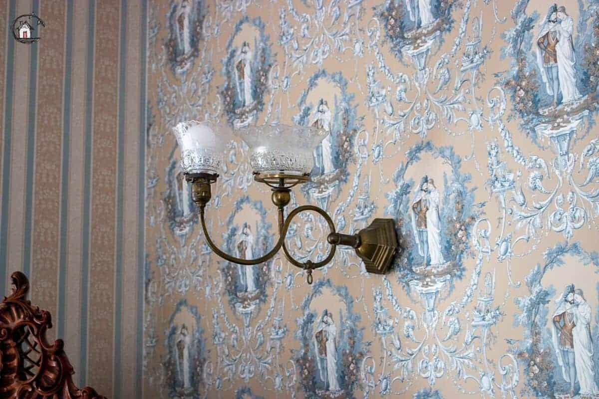 Photo of vintage wallpaper and light fixture in the Vrooman Mansion.