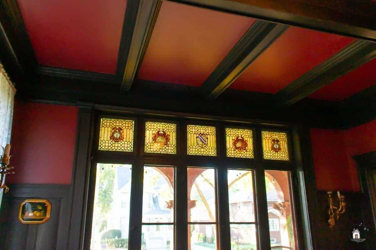 Photo or red ceiling with dark wood coffering, and stained glass windows in the Vrooman Mansion.