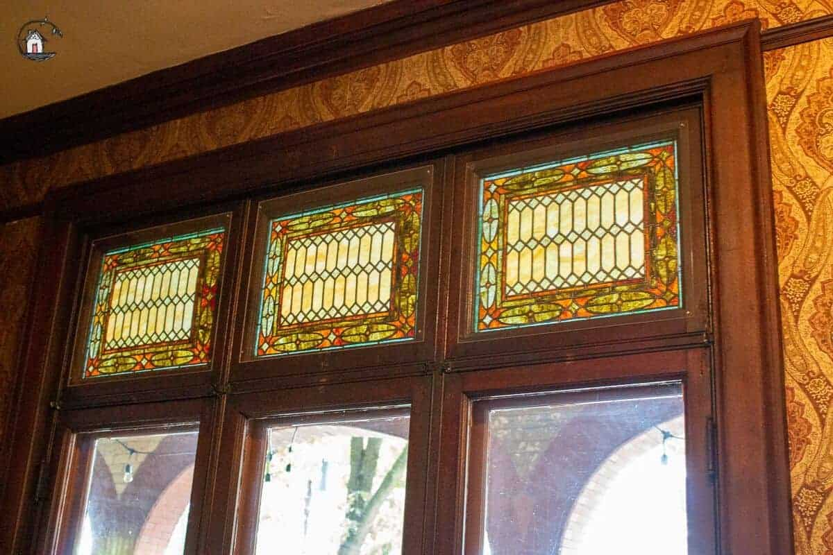 Photo of three stained glass windows in the Library of the Vrooman Mansion.
