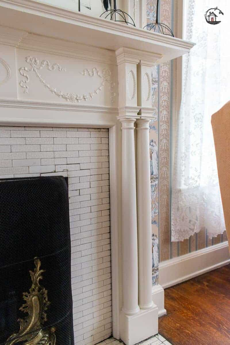 Photo of detailed fireplace surround with white columns and mantel in the Vrooman Mansion.