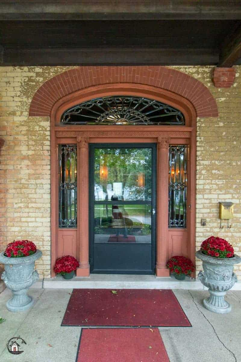 Photo of entrance to the Vrooman Mansion, with glass door and leaded glass sidelights and arched transom.
