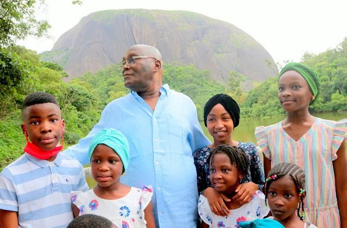 Atiku and Children smiling behind the Aso Rock