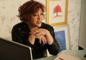 brunette in black blouse sitting at desk